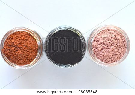 Three different mineral clays for facial masks - pink clay, red clay and activated charcoal in glass jars top view on white