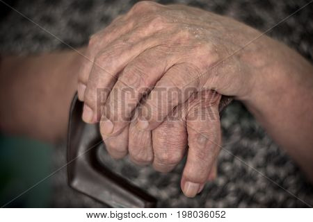 Old man sitting with his hands on a wooden walking stick