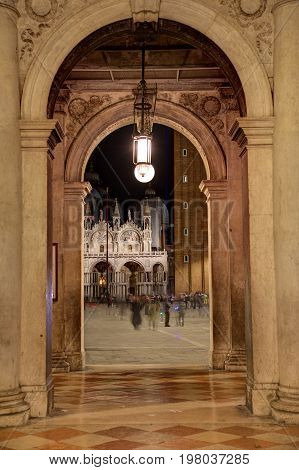 A Venetian passageway with a lone light in the arch.