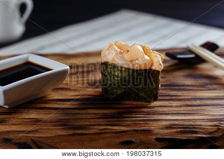 Appetizing Piquant One Nigiri Sushi With Scallop, Served On Wood