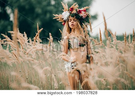 Beautiful little girl in image of nymph in floral head wreath stands with closed eyes among grasses on meadow.
