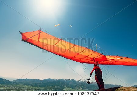 Hang-glider starting to fly over the mountains.