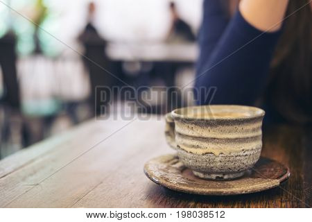 Closeup image of a woman sitting in cafe with ceramics cup of hot coffee on vintage wooden table in cafe