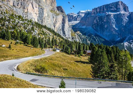Indian summer in the Tyrol. The concept of extreme and ecological tourism. Impressive ridge of dolomite rocks. Picturesque road through the Sella Pass, Dolomites