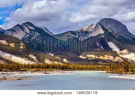 Impressive trip to the Rocky Mountains. Indian summer in the Rockies of Canada. Rocks and lakes under flying clouds. Concept of active and ecological tourism