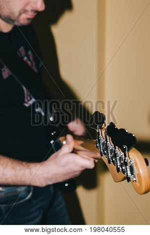 Bass guitar in selective focus. Unrecognizable guitarist, hobby for adults. Music recording process