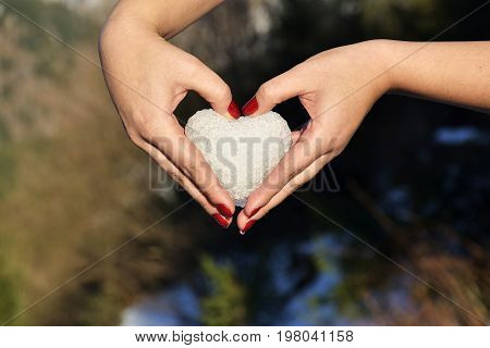 The Heart made with snowball in female hands Valentines Day Concept
