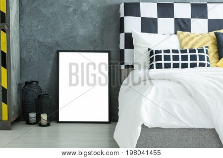 Yellow pillow on king-size bed with bolster with checkered pattern in dark bedroom