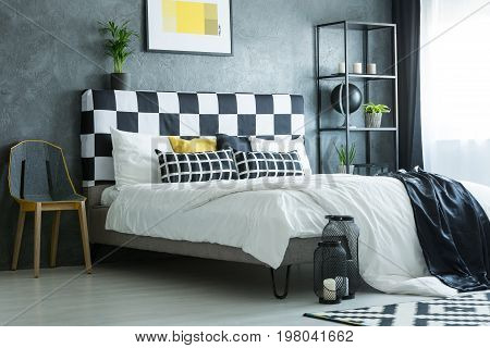 Design chair next to king-size bed with plant on bolster and candles in front of bed