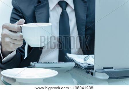 Businessman calculating the information with laptop and holding the coffee cup business concept