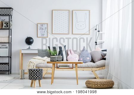 Pastel girly room with simple sofa with decorative pillows