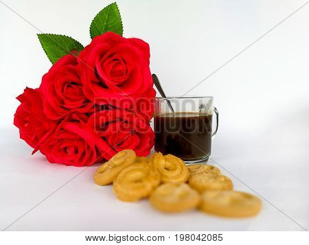 the transparent mug of a cappuccino decorated with a flower and cookies a still life on a subject hot drinks
