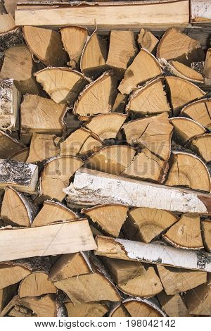The birch firewood is stacked. Natural wood background.
