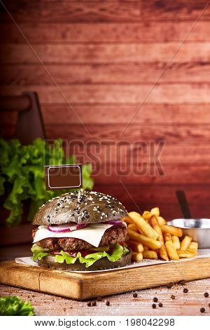 Hamburger served on wooden planks. Homemade hamburger with lettuce and cheese