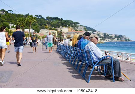 NICE, FRANCE - JUNE 4, 2017: People at the famous Promenade des Anglais walking and sitting in the characteristic blue chairs facing the Mediterranean sea in Nice, in the French Riviera, France
