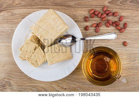 Heap Of Peanuts, Broken Peanut Halva, Tea And Teaspoon On Table