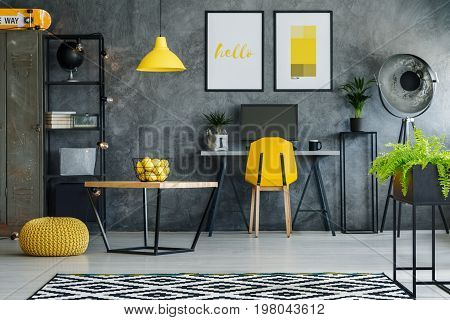 Stylish room with gray textured wall desk posters and computer
