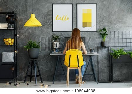 Girl sitting at her desk in posters mock-up interior with study space and modern yellow chair