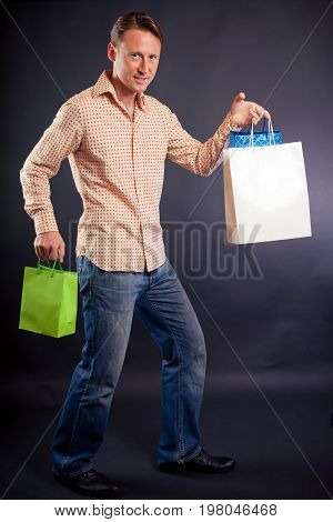 studio shot of a young man enjoying his shopping spree