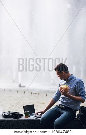 Male workaholic business lunch outdoors. Modern technology, busy man on street with laptop