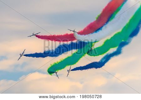 Airplane Group Fighter Against The Background Of Color Smoke