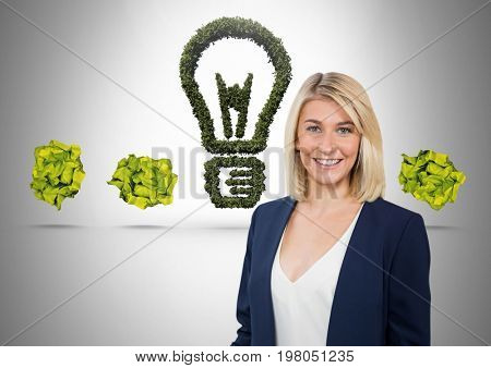 Digital composite of Woman standing next to green nature light bulb with crumpled paper balls