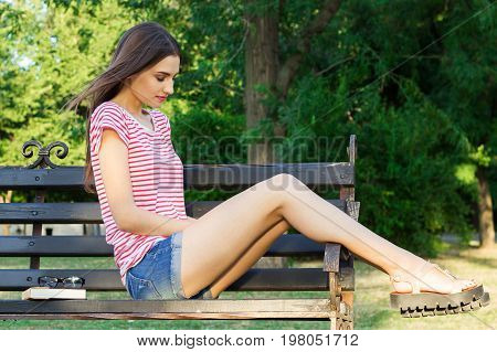 Sad young beautiful girl looking thoughtful about troubles on the bench in the park