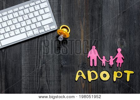 Adopt word, paper silhouette of family on dark wooden table background top view.