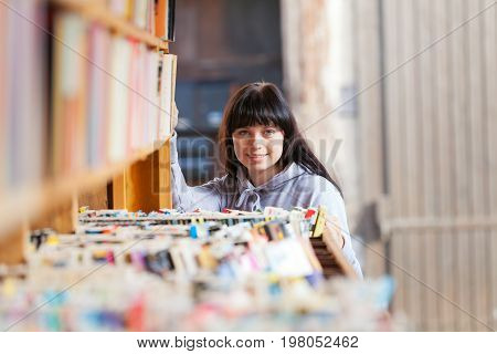 a young woman is looking at books in a bookstore
