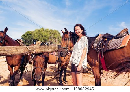 young woman with horses on horse ranch
