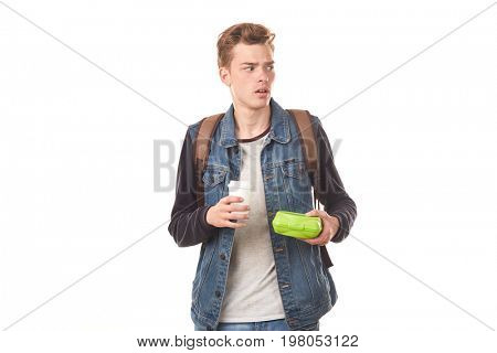 Portrait of schoolboy holding lunchbox and paper coffee cup