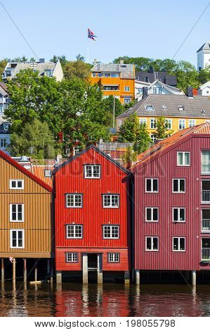 Famous wooden colored houses in Trondheim city Norway. Colorful houses on stilts and flag of Norway in sunny day.