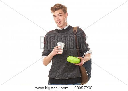 Handsome college boy holding lunchbox and paper cup of coffee