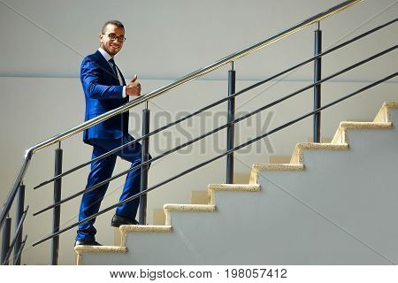 Stairs To Success. Young Smiling Businessman Climbs The Stairs.