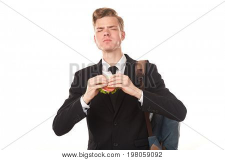Portrait of college student in black suit eating sandwich against white background