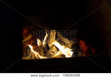 Smoldering fire in the oven and dark background