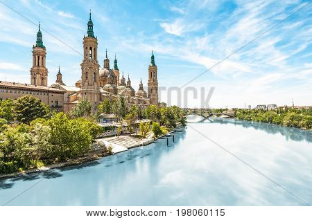Scenery landscape with Basilica of Our Lady of Pillar. Blue sky reflects in clear water. Green trees along river. Famous church with beautiful architecture. Famous tourist place in Spain Europe.
