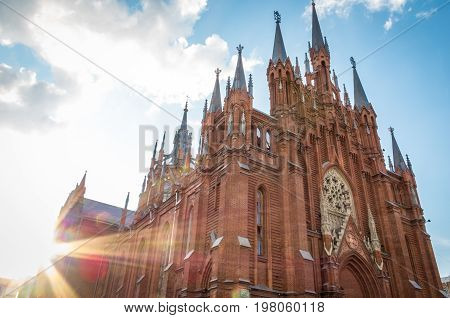 Sunburst on the exterior facade with its arched windows of an old red brick Catholic church against a cloudy blue sky in a spiritual religious background.