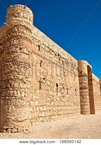 ancient desert castle with blue sky in background in Jordan