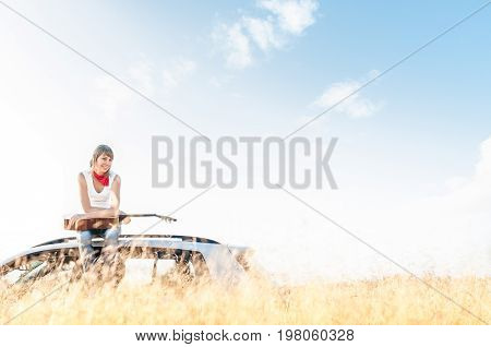 Young smiling girl sitting on her car with guitar in hands with wheat field in foreground and blue sky in background behind woman. Freedom and music. Active leisure and hobby.