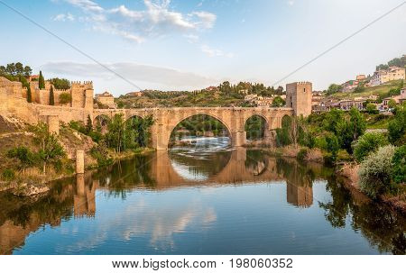 Beautiful landscape of Toledo in Spain. Stone bridge across calm river. Blue sky reflected in crystal clear water. Big fort and country houses in background. Popular tourist place in Europe.