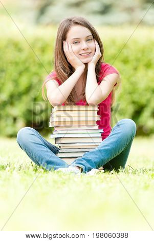beautiful and happy young student girl sitting on green grass pile of books under her hands smiling and looking into the camera. Summer or spring green park in background
