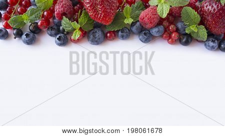 Various fresh summer berries on white background. Ripe raspberries blueberries blackcurrants and red currants mint. Berries at border of image with copy space for text. Background berries. Top view.