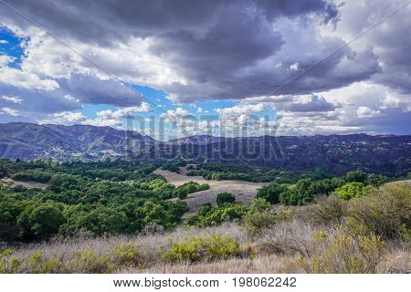 Dramatic clouds and a blue sky over Topanga Canyon's oak trees and chaparal
