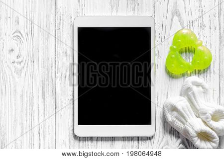 Mockup for adoption concept. Tablet PC on light wooden background top view.