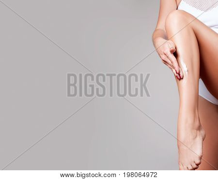 Body Care. Woman Applying Moisturizer Cream On Legs.