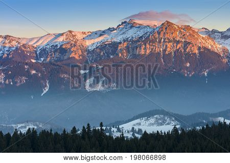 Fantastic view in winter season with the peak of Bucegi massif in the warm colorful sunset light landscape seen from resort Fundata Cheile Gradistei Romania.