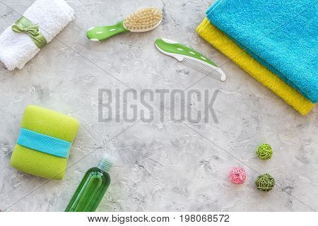 Preparation for spa therapy. Towels, washcloth, lotion and brush on grey background top view.
