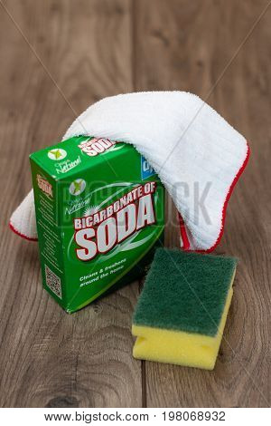 August 2nd, 2017, Cork, Ireland - a box of bicarbonate soda on top of a wooden table with a plastic scrubber and a cloth