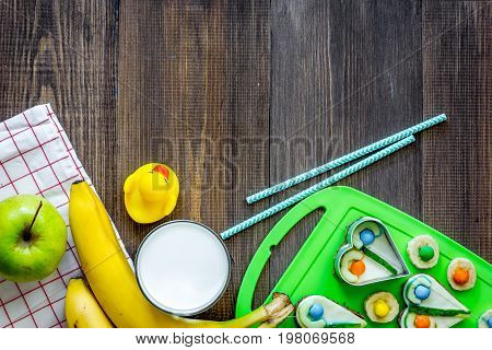Preparing quick lunch for school child. Fruits on dark wooden table background top view copyspace.